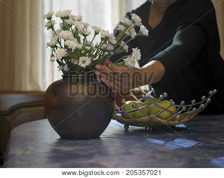 Woman arranging bouquet in a vase indoor cropped image