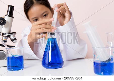 Asian girl playing as a scientist to experiment with laboratory equipment and microscope cameras in scientific laboratory.