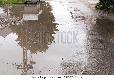 Water accumulate in the puddle on the asphalt road in the hole after heavy rain