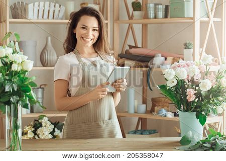 Young female florist working with flowers holding digital tablet