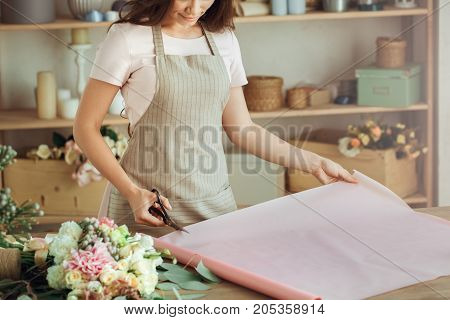 Young female florist working with flowers gift paper
