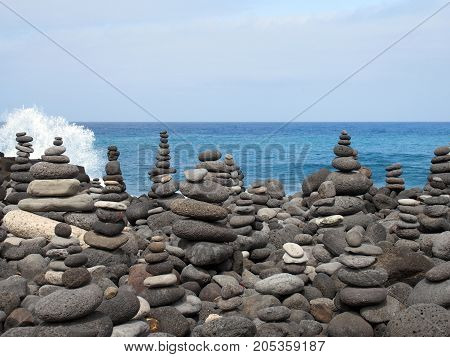 rock art piles and towers of grey stones and pebbles on a beach with blue sky and blue sky in tenerife with breaking waves