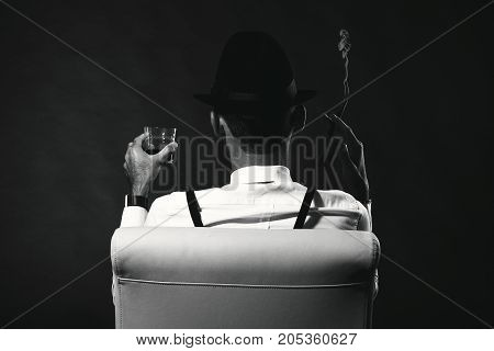 An Unidentified Man In A Suit And Hat With A Cigar And Whiskey Staring Into The Distance. View From