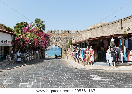 RHODES, GREECE - AUGUST 2017: Ancient arch in old wall of Rhodes town with purple bougainvillea flowers in Rhodes town on Rhodes island, Greece