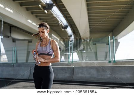 Fitness model standing under a bridge, opening a water bottle