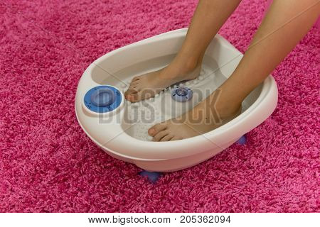 Children's Feet In A Vibrating Foot Massager. Electric Massage Foot Bath Home On A Pink Background.