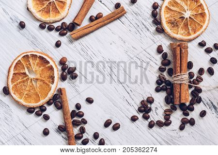 Dried oranges of coffee and cinnamon on a white wooden surface top view