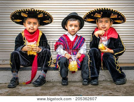 Three Boys In Caballero Costumes Sit On A Ledge Eating Potato Chips