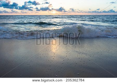 gentle waves crashing on the shore and reflecting sunlight