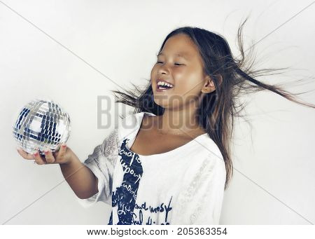 Happy teenager girl with a mirror ball and flying hair on white background