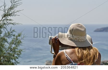 young woman is watching trough a telescope