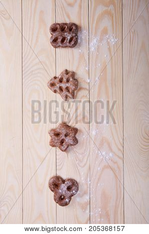 A lot of chocolate cookies in a different form on a light brown wooden background. Tasty homemade biscuits.