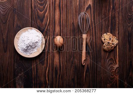 The process of making homemade cookies on a dark brown wooden cooking table. Ingredients for baking biscuits.