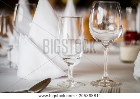 Elegant dining table setting with napkin and wine empty glasses
