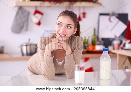 Happy young woman having healthy breakfast in kitchen.