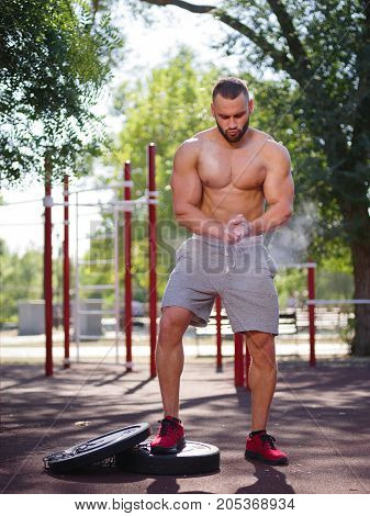 A hot, sexy young man with muscular body training outdoors. Handsome sportsman exercising in gym.