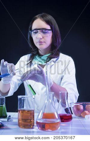 Medicine Concepts. Female Laboratory Assistant in Protective Gloves During Scientific Experiment With Liquid Components in Lab. Vertical Image Composition