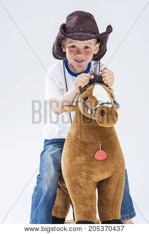 Natural Portrait of Happy Smiling and Glad Caucasian Little Boy in Cowboy Clothing With Symbolic Plush Horse Against White.Vertical Composition