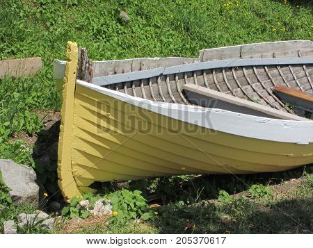 Yellow old row boat discarded by side of the road
