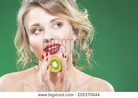 Fruit Series. Portrait of Curious Caucasian Blond Model Posing With Slice of Green Juicy Kiwi Fruit and Dreaming. Against Green Background.Horizontal Shot