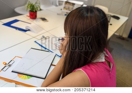 Young Asian employee working alone in the office