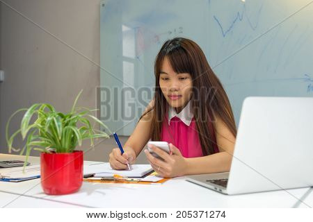 Young businesswoman searching information on smart phone and write it down