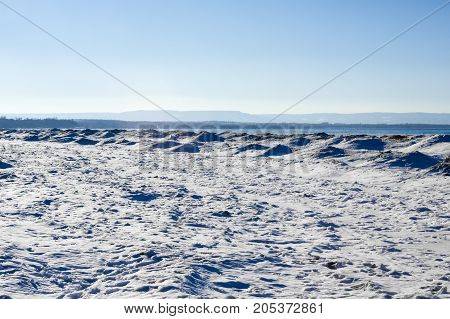 frozen ice snow and sand dunes on beach in winter by lake under clear blue sky. with hills in distance near Georgian Bay Ontario Canada.
