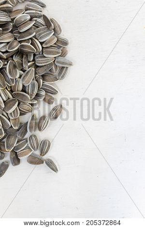 raw organic white and black freshly harvested sunflower seeds on white painted wooden rustic table with copy space