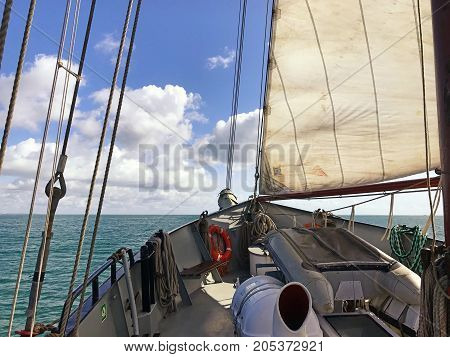 Ketch sailing boat in the sea with its sail up looking from the deck of the boat. With space for text.