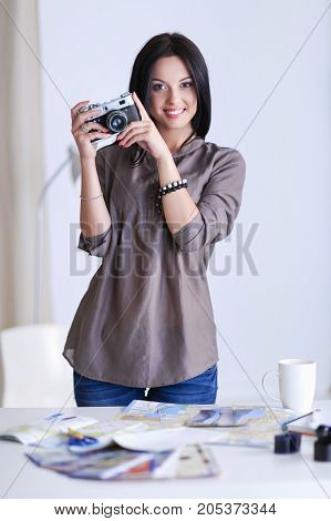 Portrait of a young beautiful photographer woman near table.