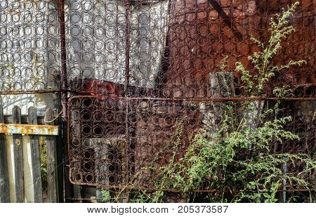 Homemade rustic fence made from old spring mattress, metal sheets and banner fabric. Abstract grunge background