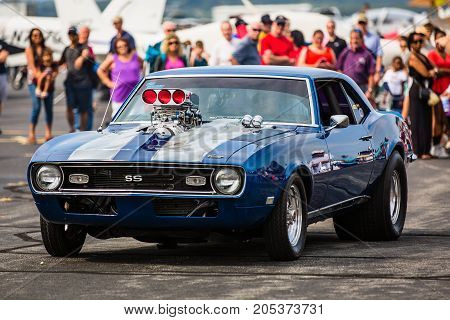 LOUDOUN COUNTY VIRGINIA - 24 SEPTEMBER 2016: A modified classic Camaro drives past a group of onlookers