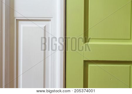 Close up of green interior door with white casing, horizontal aspect
