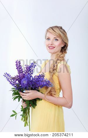 Beautiful smiling girl with flowers on a white background.