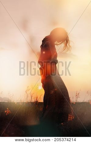 silhouette of beautiful young woman at sunset