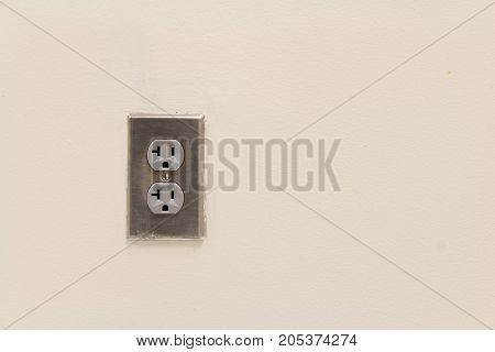Silver metal outlet cover on tan wall, horizontal aspect