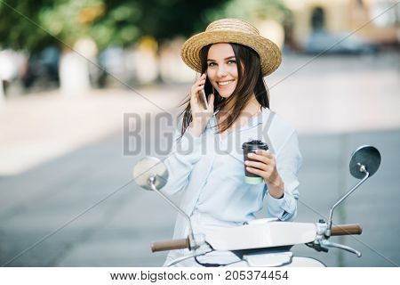 Happy Young Woman Drinking Takeaway Coffee Near Her Moped And Talking Phone On City Street