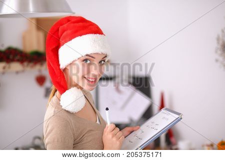 Happy young woman smiling happy having fun with Christmas preparations wearing Santa hat.