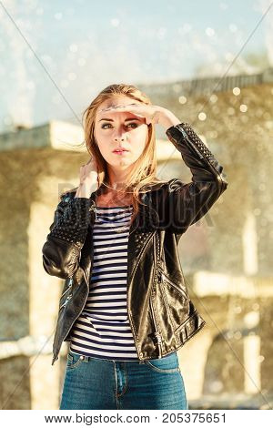 Fashion young blonde woman casual style posing against city fountain
