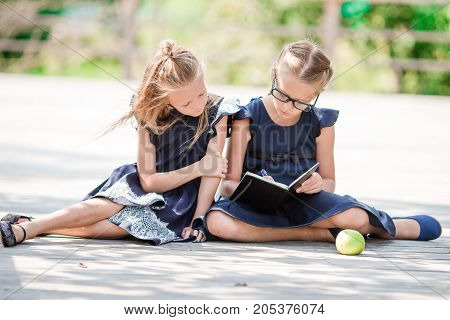 Adorable little school girls with notes and pencils outdoor.