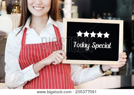 Smiling woman holding Today's special and five start board sign over blur cafe background food and drinks recommended concept