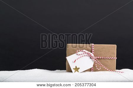Present box with tag on a black background