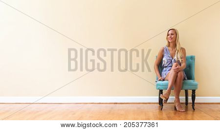 Young woman with blond hair sitting in a big room