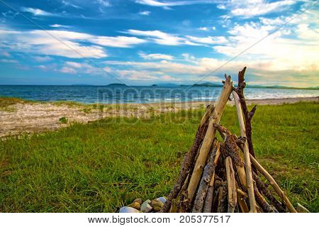 bonfire of wood on the beach near the sea. around the decorated stones. under the blue sky