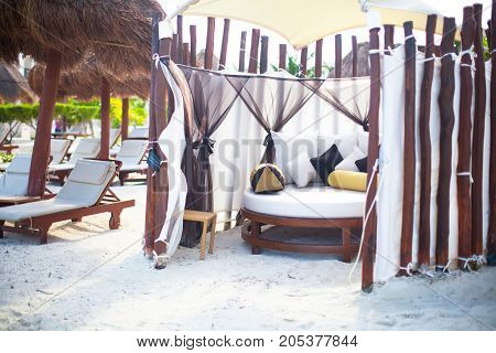 Chaise lounges under an umbrella on sandy beach