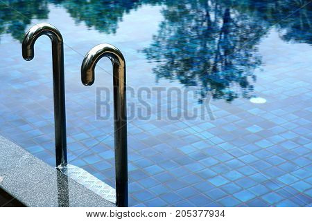 The swimming pool ladder in clean water with shadow of the tree.