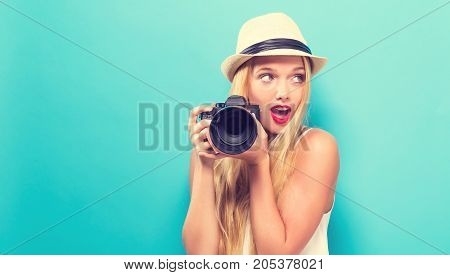 Young woman comparing professional camera on a solid background poster