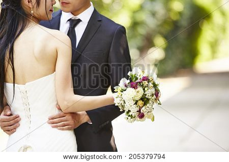 asian wedding couple hugging each other focus on the bouquet.