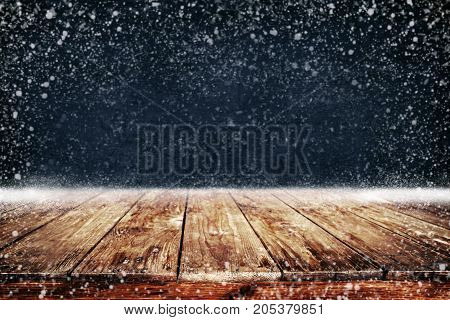 Christmas and New year background with wooden deck table and snowfall. Empty display for product montage. Rustic vintage Xmas background.