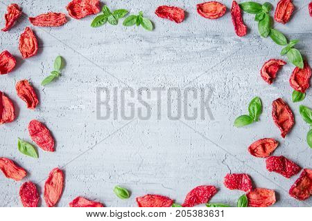 background of sun dried tomato slices with basil leaves on concrete table. top view. space for text